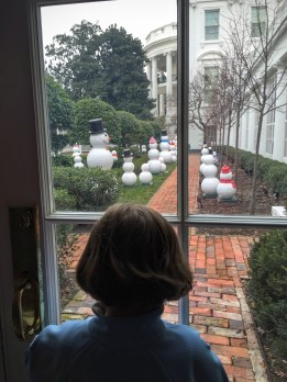 Lilly looking over the lawn of snowmen